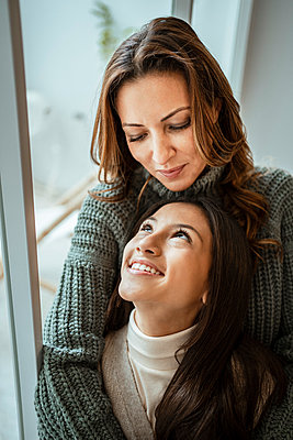Beautiful mother and daughter looking at each other while sitting by window at home - p300m2257156 by Rafa Cortés