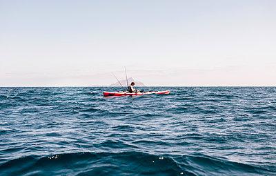 Young male sea kayaker looking at smartphone while fishing, Santa Cruz Island, California, USA - p924m1506723 by JFCreatives