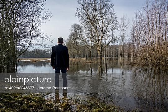 Mann im Anzug steht im Wasser - p1402m2248677 von Jerome Paressant