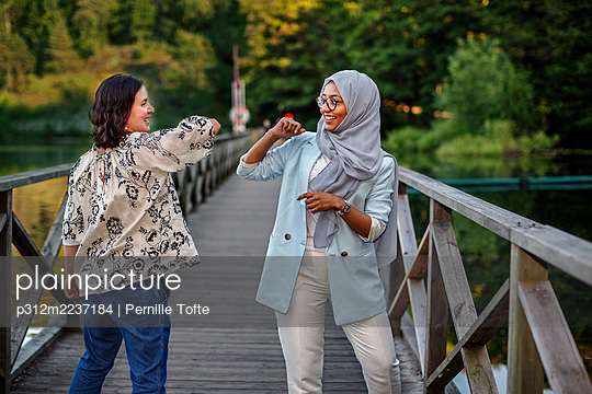 Female friends using elbow greeting - p312m2237184 by Pernille Tofte