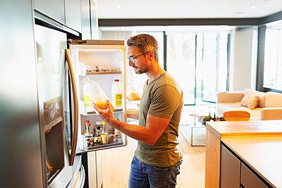 Man holding orange juice at open refrigerator in kitchen - p1023m2196687 by Paul Bradbury
