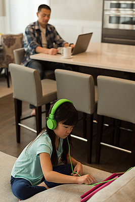 Girl using digital tablet while father using laptop in background at home - p1315m1565963 by Wavebreak