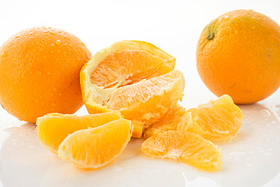 Peeled and whole oranges - p1427m2038487 by Tetra Images