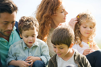 Family relaxing together outdoors - p624m1487345 by Eric Audras