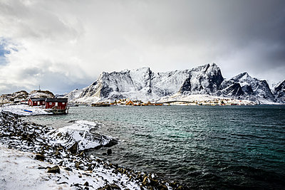 Snowy mountains overlooking rocky coastline, Reine, Lofoten Islands, Norway,Reine, Lofoten Islands, Norway - p1100m2084167 by Mint Images