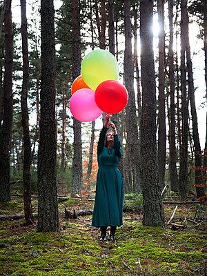 Frau mit Luftballons im Wald - p1105m2134525 von Virginie Plauchut