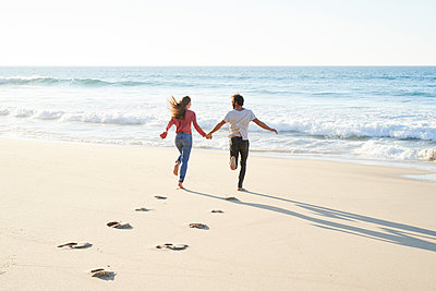 Young couple running on beach - p1124m1508605 by Willing-Holtz