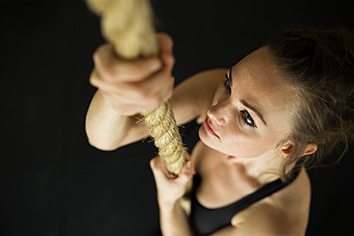 High angle view of woman holding rope while exercising in gym - p1166m1545977 by Cavan Social
