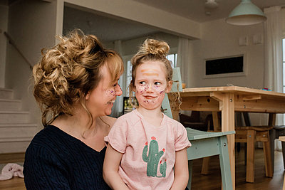 mother and daughter pulling silly faces whilst playing dress up - p1166m2165844 by Cavan Images