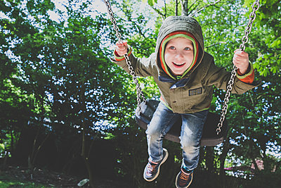 Portrait of happy little boy on a swing - p300m2160581 von Irina Heß