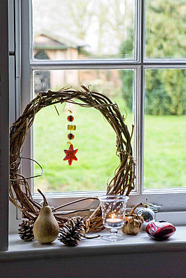 Detail of natural christmas decorations on a window sill with a candle - p349m790513 by Polly Eltes