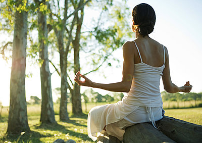 Woman doing yoga pose outdoors - p6241693f by Alix Minde
