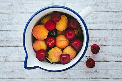 Aprikosen und Kirschen in einer Kanne - p946m823756 von Maren Becker