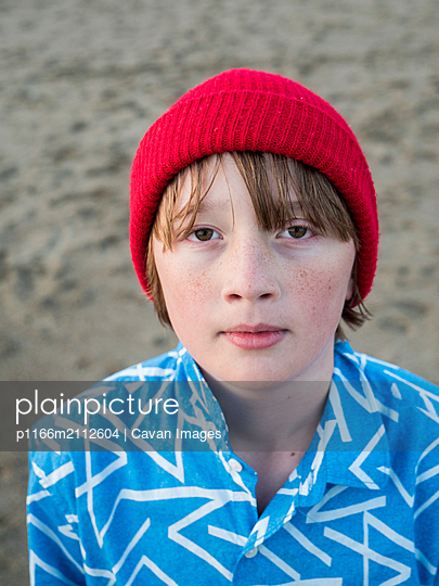 High angle portrait of boy standing on sand at beach - p1166m2112604 by Cavan Images