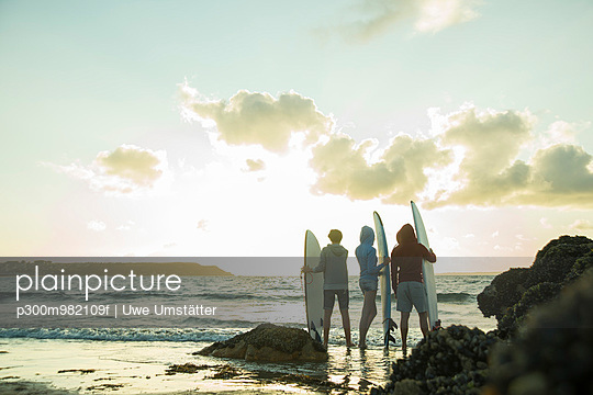 Three teenagers standing on the beach with their surfboards looking at horizon - p300m982109f by Uwe Umstätter