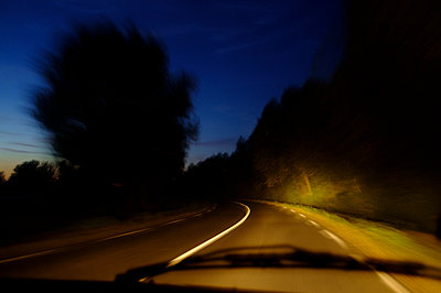 Speeding drive view of a road curve in the night - p1096m2063666 by Rajkumar Singh