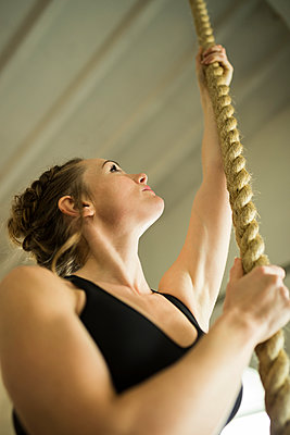 Low angle view of woman holding rope while exercising in gym - p1166m1545978 by Cavan Social