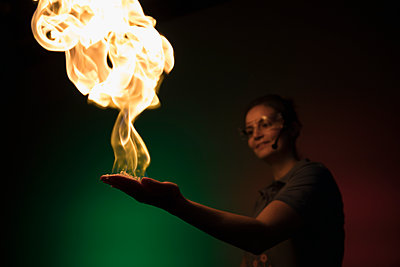 Scientist creating fire demonstration in palm of hand in science center - p1192m1194210 by Hero Images