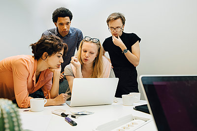 Multi-ethnic colleagues planning strategy while looking at laptop in illuminated office board room - p426m2195005 by Maskot