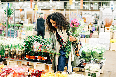 Female florist selecting flowers at new Covent Garden flower market, London, UK - p429m1418075 by Alys Tomlinson
