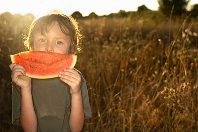 Boy eating watermelon in tall grass - p429m1450454 by Leon Sosra