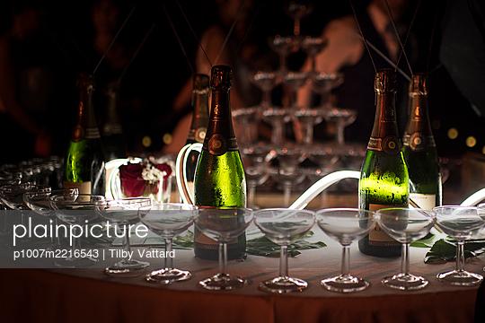 Champagnerflaschen und Gläser auf Hochzeitsfeier - p1007m2216543 von Tilby Vattard