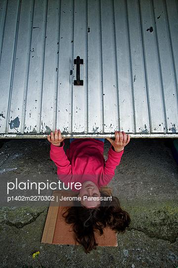 Girl under a garage door - p1402m2270302 by Jerome Paressant