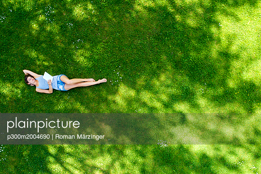 Young woman lying on meadow, using tablet - p300m2004690 von Roman Märzinger