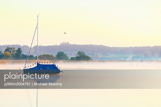 Germany, Bavaria, Chiemsee, covered sailing boat in the evening light - p300m2004761 von Michael Malorny