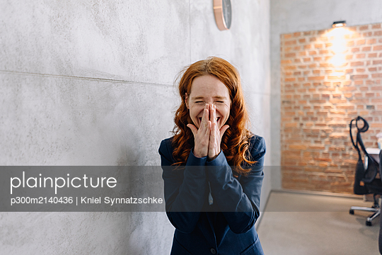 Laughing redheaded businesswoman in office