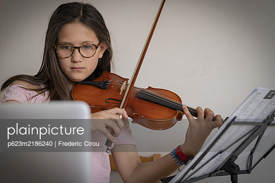 Girl attending homeschooling online violin classes - p623m2186240 by Frederic Cirou