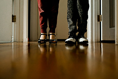 Two young children wearing heels and shoes standing in a hallway - p1166m2268990 by Cavan Images