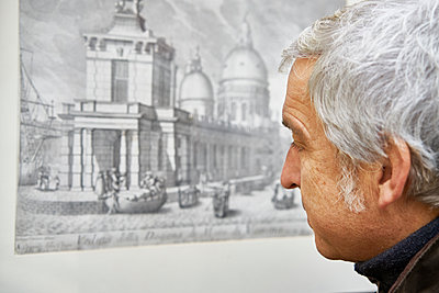 Man with gray hair looks at a work of art - p1312m2082182 by Axel Killian