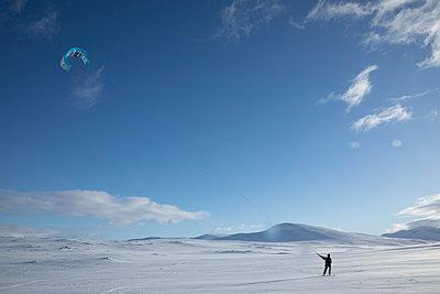 Man snowkiting in the Swedish wilderness - p1687m2278799 by Katja Kircher