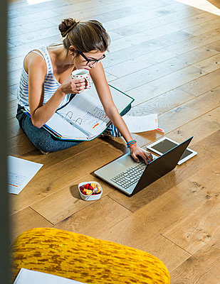 Young woman sitting on wooden floor with file folder and laptop - p300m1047549f by Uwe Umstätter