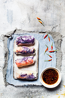 Vegan rice paper wraps (vietnamese summer rolls), filled with cabbage, carrots, bell pepper, rice odles, and dipping sauce - p300m1587561 by Susan Brooks-Dammann