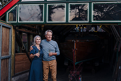 Senior couple standing in front of boathouse with glass of champagne - p300m2156234 von Gustafsson