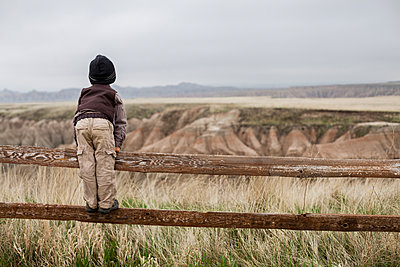 Boy wearing explorer costume standing on wooden fence - p343m1446668 by Steve Glass