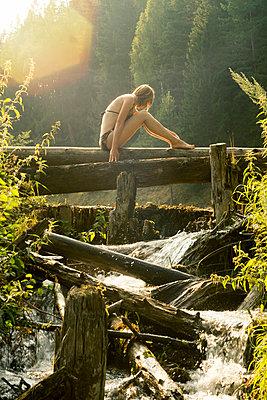 Caucasian woman sitting on log over waterfalls - p555m1303608 by Aliyev Alexei Sergeevich