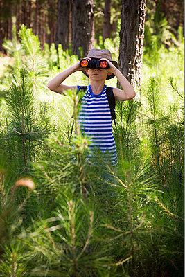 Boy using binoculars in woods - p623m1495190 by Frederic Cirou