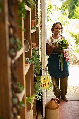 Portrait confident female florist with flower bouquet in shop doorway - p1023m2261869 by Martin Barraud