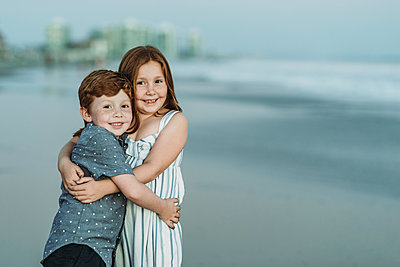 Portrait of brother and sister hugging at the beach at dusk - p1166m2136552 by Cavan Images