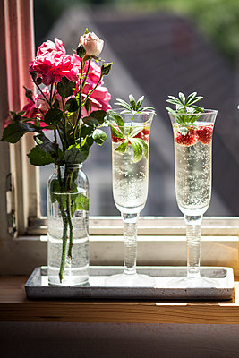 Two Champagne glasses of may wine with raspberries on window sill - p300m1499270 by Susan Brooks-Dammann