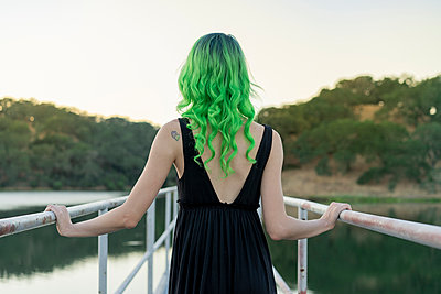 Back view of young woman with dyed green hair standing on a footbridge at lake - p300m2023608 by VITTA GALLERY