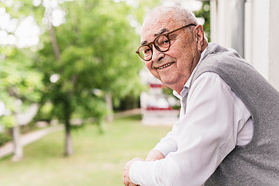 Portrait of smiling senior man on balcony - p300m2189532 by Uwe Umstätter