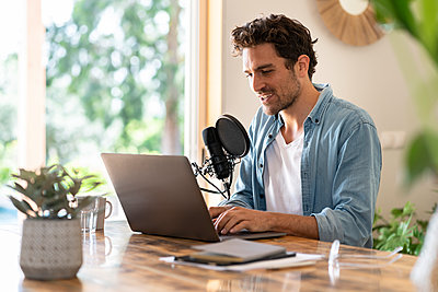 Male freelancer speaking on microphone in front of laptop while recording podcast at home - p300m2276529 by Steve Brookland