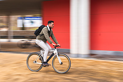 Handsome man riding bicycle by red wall - p300m2277162 by Josu Acosta