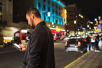Side view of man using smart phone on city street at night - p426m1114842f by Maskot