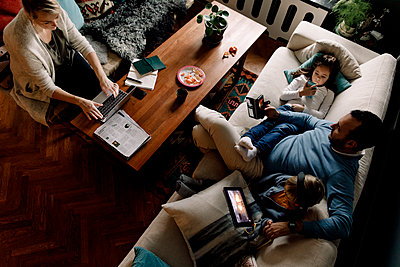High angle view of family using various technologies in living room at home - p426m2074685 by Maskot