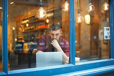 Window view of young man using laptop in cafe - p429m1418086 by Peter Muller